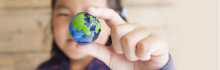 Fille tenant une bille en forme de Terre